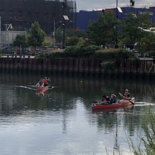 students and guides in red canoes paddle in the Gowanus Canal
