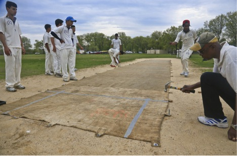 In this May 12, 2014 photo, a mat is being pounded into a cricket pitch before the start of a PSAL Cricket Match between Midwood High School and John Adams High School in Marine Park.